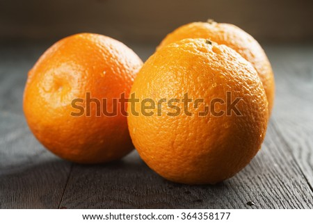 three ripe oranges on wooden table - stock photo