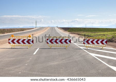 Three road signs barriers bordering a new road under construction. - stock photo