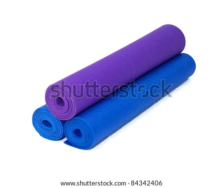 three rolled yoga exercise mats against white. - stock photo