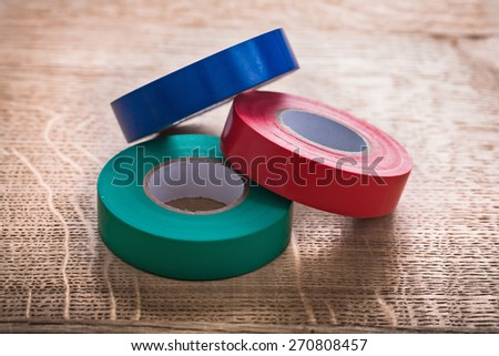 three rolls of insulating tape on wooden board construction concept  - stock photo