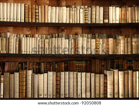 three rows of old books on a shelf - stock photo