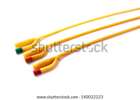 three rubber foley catheters isolated over a white background - stock photo