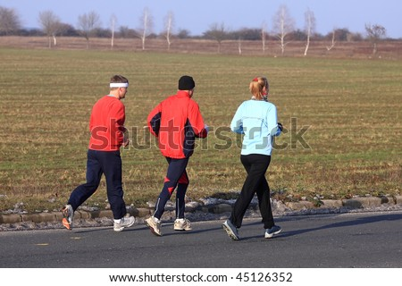 Three running in the cold winter weather - stock photo
