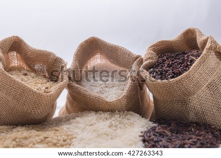 Three sack with different types of rice: brown rice, riceberry rice and white (jasmine) rice on white background. Selective focus - stock photo