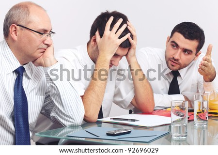 Three sad and depressed businessman sitting at table during meeting - stock photo