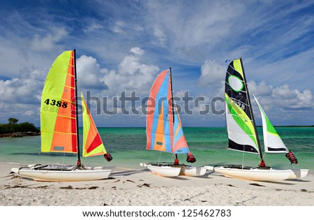 Three sail boats, catamarans, on tropical beach with blue water background - stock photo
