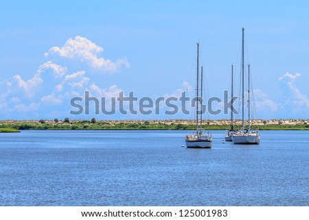 Three sailing boats anchoring near beach coastline - stock photo