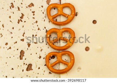 Three salted pretzels on two slices of cheese background  - stock photo