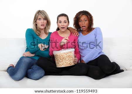 Three scared women sat on sofa watching movie - stock photo