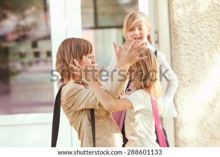 Three schoolgirls outdoors near the door of school building. Friend meet after holidays - stock photo