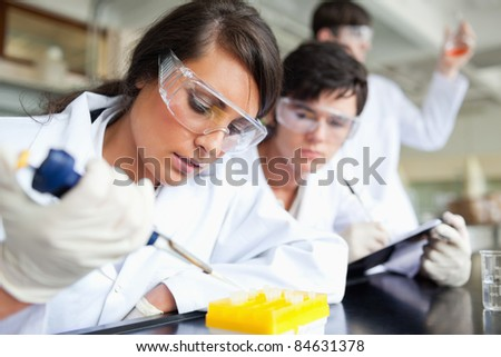 Three scientists working in a laboratory - stock photo