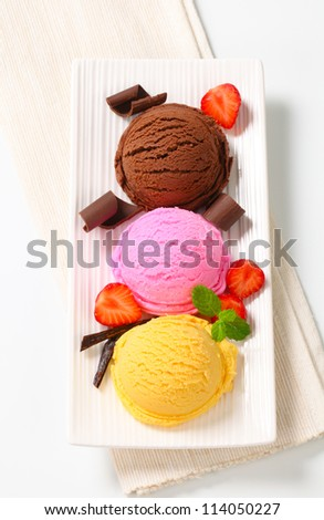 Three scoops of ice cream with strawberries and chocolate curls  - stock photo