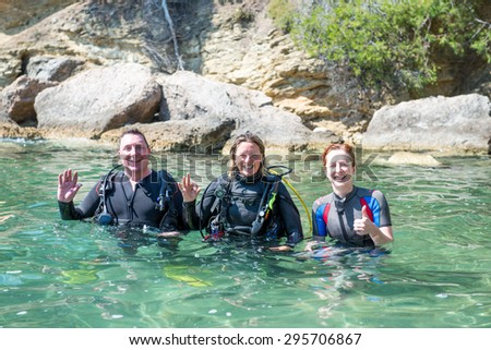 Three Scuba Divers standing in shallow water before a dive.Two of them are wearing their scuba equipment. - stock photo