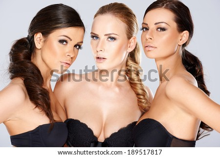 Three sensual beautiful beguiling young women wearing black lingerie looking seductively at the camera as they pose together in a group - stock photo