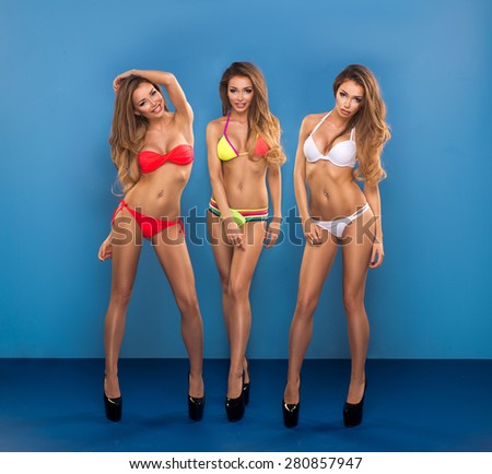 Three sexy attractive blonde woman posing in fashionable swimsuit in studio - stock photo