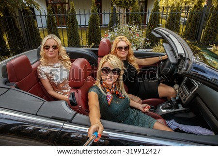Three sexy blond girls in sunglasses posing in a cabriolet car. - stock photo