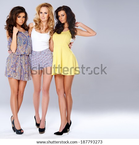 Three sexy chic young women in summer fashion standing arm in arm showing off their long shapely slender legs, studio background - stock photo