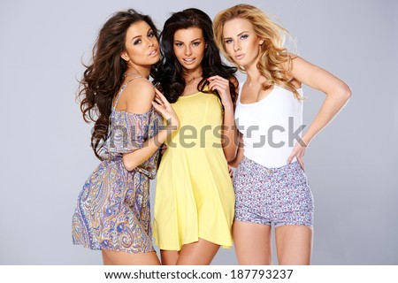 Three sexy chic young women in summer fashion standing arm in arm studio background - stock photo