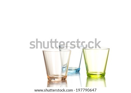 Three shot glasses colored brown, blue and green on white background - stock photo