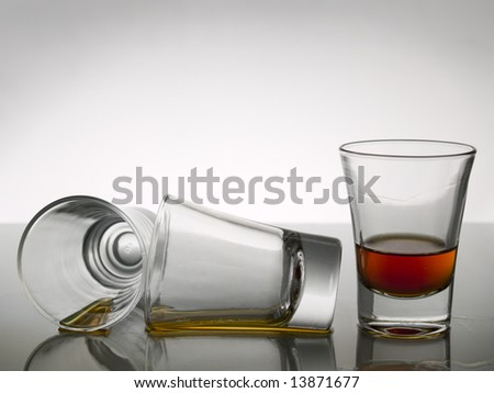 Three shots of whisky on white background over gray floor - stock photo