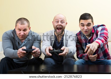 Three shouting males playing video games at house party - stock photo