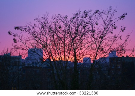 three silhouette and impressive sunset on city skyline - stock photo