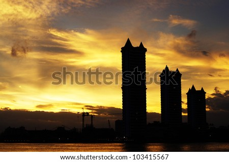 Three silluate buildings beside the river and the golden sky - stock photo