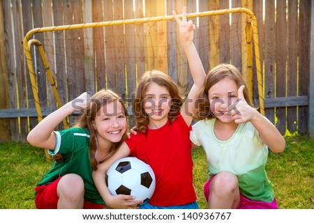 three sister girls friends soccer football winner players on the backyard - stock photo