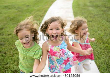 Three sister girls playing running on the green park outdoor - stock photo