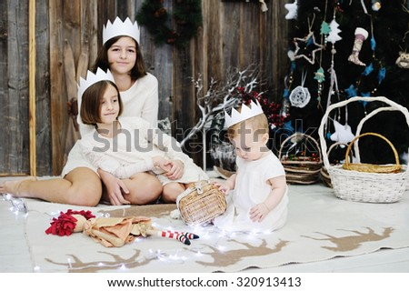 Three sisters age of 10 month, 7 and 12 years in white dresses and crowns posing in front of the christmas tree - stock photo
