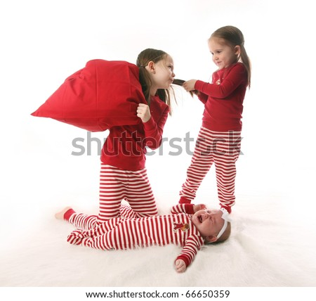 Three sisters dressed in Christmas pajamas. Two older girls are pulling hair and having a pillow fight while the baby is crying. - stock photo