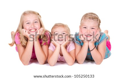 Three sisters laying on white background smiling - stock photo