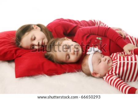 Three sisters sleeping snuggled together, dressed in Christmas pajamas - stock photo