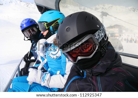 Three skiers in helmets and goggles ride on funicular in mountains. Focus on boy. - stock photo