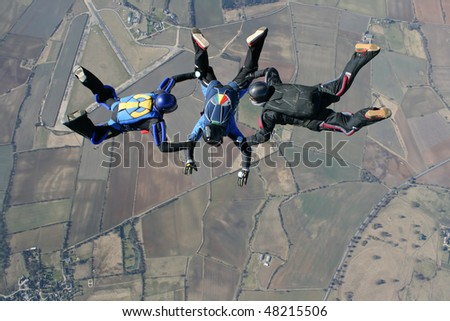 Three skydivers performing formations - stock photo