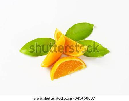 three slices of fresh orange with leaves on white background - stock photo