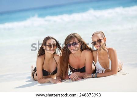 Three slim young girls in bikinis on the beach. summer holidays and vacation - girls in bikinis sunbathing on the beach.  - stock photo