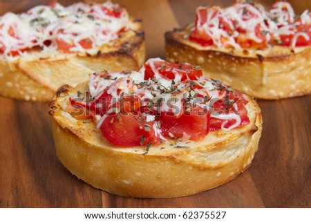 three small bruschetta bites on a cutting board - stock photo