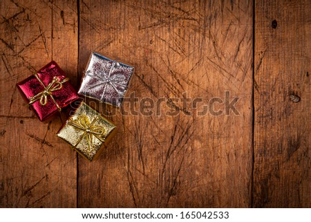 Three small Christmas present box on vintage wooden background. Above view.  - stock photo