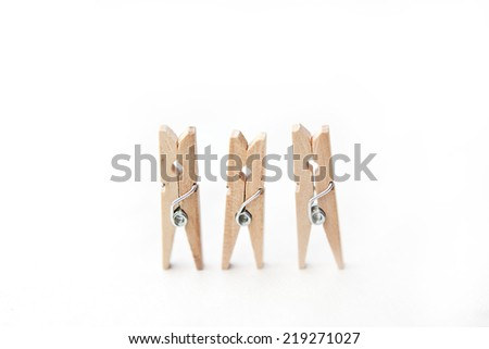 Three small clothespin tweezers in a row isolated on a white background. - stock photo