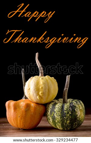 three small decorative pumpkin on wood with happy thanksgiving written - stock photo