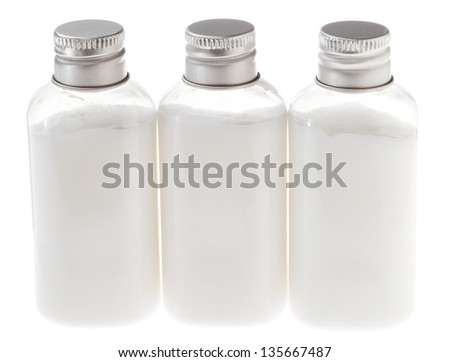 Three small plastic bottles filled with white cosmetic cream and sealed with a silver metal cap. The white contents of the bottle can be lotion, shampoo, conditioner, liquid soap, shower gel etc. - stock photo