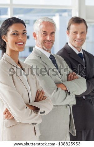 Three smiling business people standing together with their arms folded - stock photo