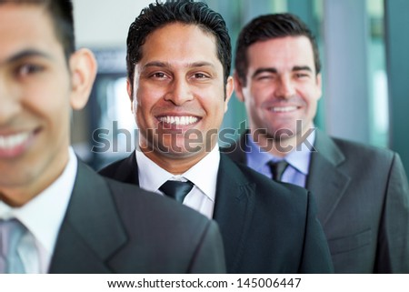 three smiling businessmen standing in a row - stock photo