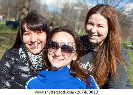 Three smiling Caucasian attractive women looking at camera - stock photo