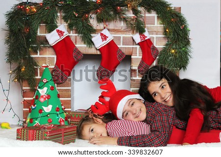 Three smiling children lying near Christmas decorated fireplace, winter holiday family concept - stock photo