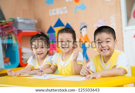 Three smiling children sitting at table in the kindergarten - stock photo