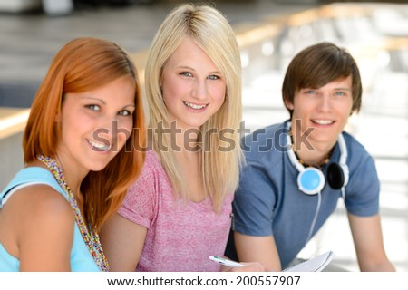 Three smiling college student friends sitting together looking at camera - stock photo