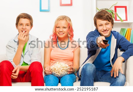 Three smiling friends eat popcorn together on sofa - stock photo