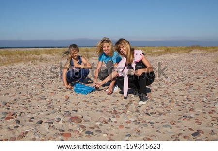 Three smiling girls on an empty beach collect stones - stock photo